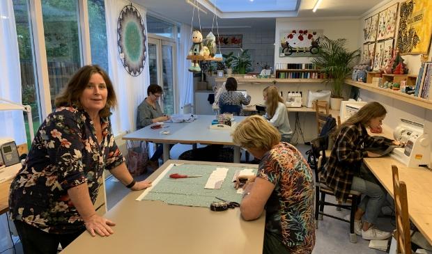 <p>Coupeuse Anne-Marie Smulders (l) in haar naaischool met de dames van de donderdagavond.</p>