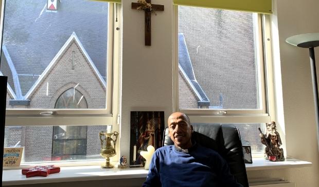 Pastoor Kaleab Masresha Shiferaw in zijn woonkamer naast de kerk.