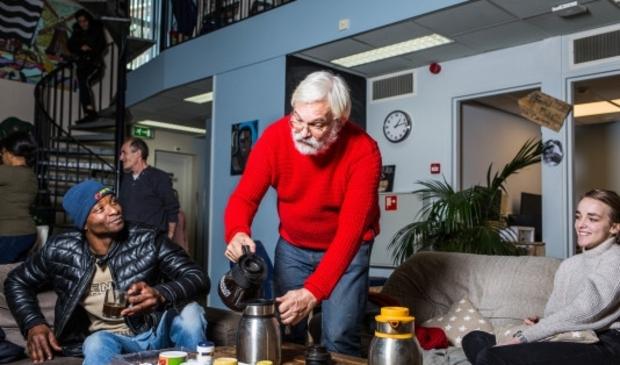 <p>Medewerker Hans schenkt in de buurthuiskamer een kopje koffie in.</p>