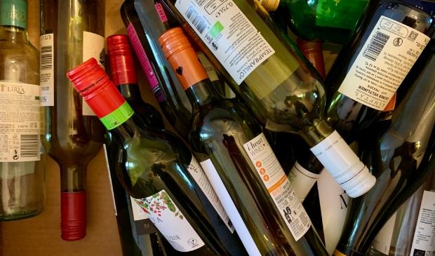 <p>Lege drankflessen onderweg naar de glasbak.</p>