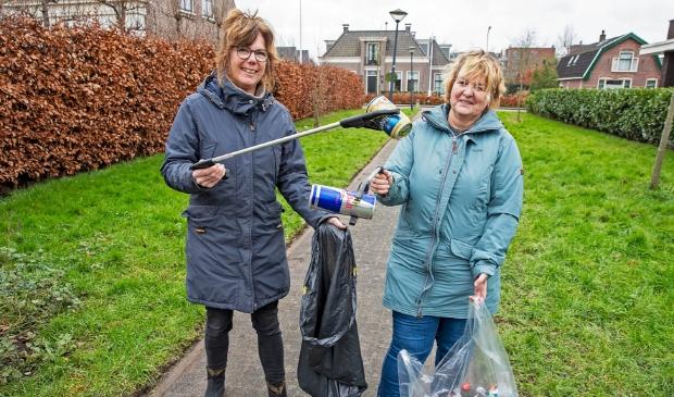 <p>Sandra (l) en Linda ruimen met een prikstok afval op van de straat. &quot;We hopen mensen wakker te schudden en aan te sporen om ook iets te doen.&quot;</p>