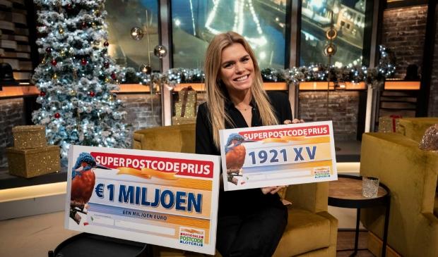 <p>Nicolette van Dam toont de winnende postcode van de Super Postcodeprijs van de Postcode Loterij.</p>