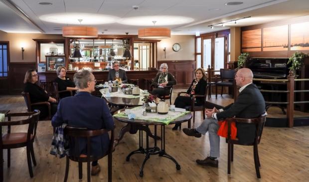 <p>In het Grand Caf&eacute; van woonzorglocatie De Hoge Hop in Hoorn, waar voor de coronamaatregelen activiteiten en samenkomsten voor bewoners plaatsvonden, bespreken de deelnemers aan het werkbezoek de situatie in de zorg. </p>