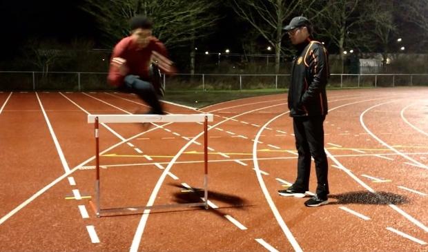 <p>Robin Korving (r) traint in de avonduren talentvolle hordelopers op de atletiekbaan van Hera.</p>