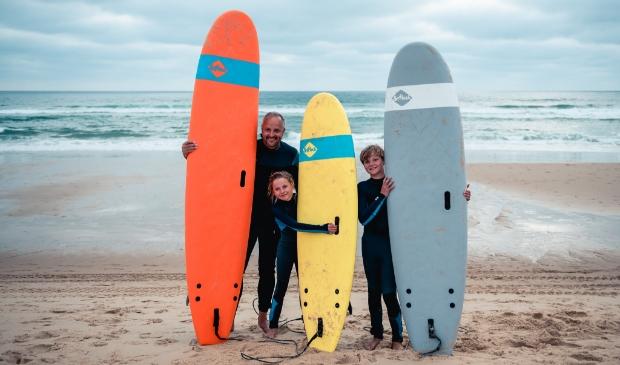 <p>Vader met zijn kinderen surfen op het strand van Bloemendaal.</p>