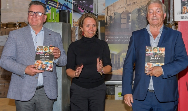 <p>De wethouders Mario Hegger en Jos Dings hebben het eerste exemplaar van het kookboek Smaak zojuist van Annet Rijser gekregen.</p>