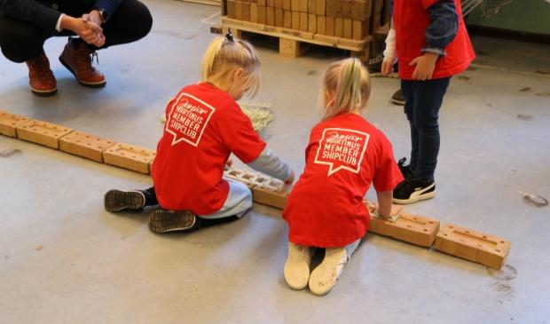 <p>Unieke start Kinderboekenweek: kleuters van De Hussel enthousiast aan het metselen.</p>