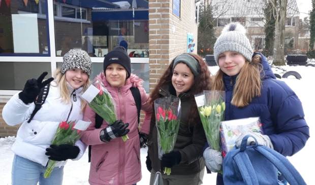 <p>Leerlingen van De Duif met een vrolijke bos tulpen voor hun ouders, als bedankje voor de inzet en begeleiding tijdens de schoolsluiting.</p>