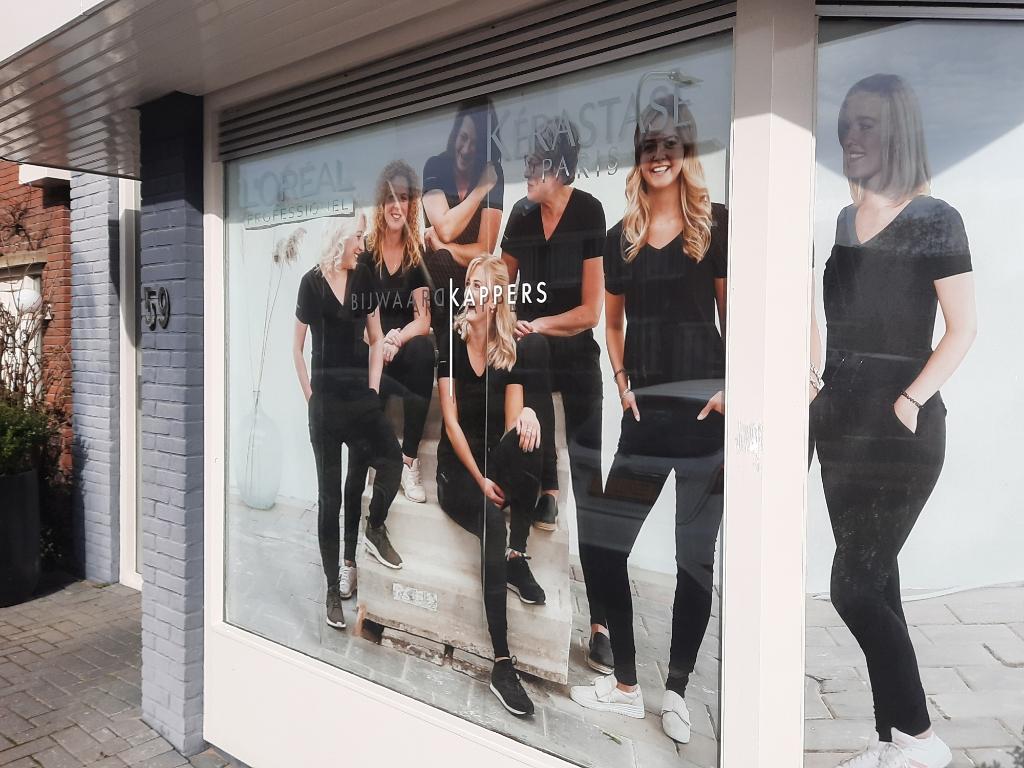 <p>Op het raam aan de Zevenhuizerlaan prijkt sinds kort een foto van de zes medewerksters van Bijwaard Kappers.</p> (Foto: Ed Bausch) © rodi