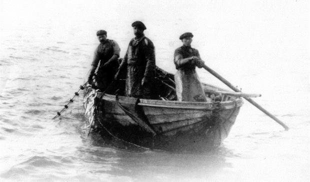 <p>Foto uit 1932 van de vissers Cees Fijma, Willem Visser en K. de Graaf tijdens de ansjovisvisserij. De staande netten met de gevangen ansjovis worden binnengehaald. Ansjovisvlet EH 97.</p>