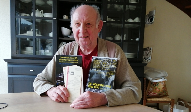 <p>Jan Holvast met twee van zijn boeken en een aantal ponskaarten, die vijftig jaar geleden werden gebruikt voor het vastleggen van persoonsgegevens.</p>