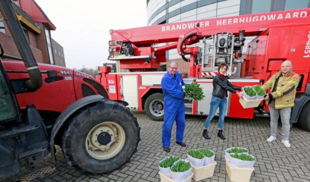 <p>De plaatselijke brandweer kreeg van kweker Marco Kroon (in blauwe overall) bossen tulpen uitgereikt.</p>