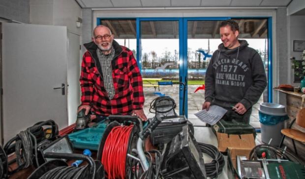 <p>Vrijwilligers Nico Molenaar (l) en Kjell van der Vlugt zijn druk bezig de elektrische apparatuur te keuren.&nbsp;</p>