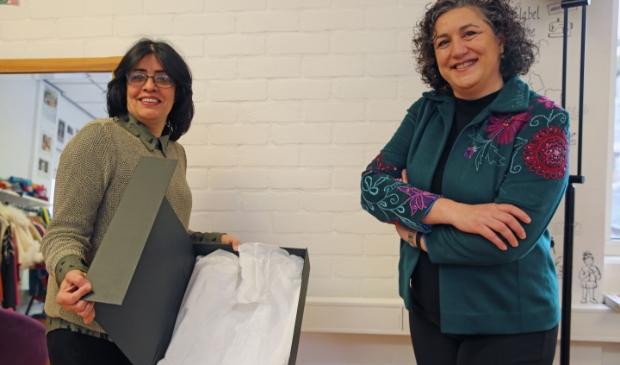 <p>Halleh Ghorashi (r) neemt het jasje in ontvangst van About a Jacket-deelnemer Heshmat Pourseif die het jasje genaaid heeft. Net als Halleh is Heshmat ook gevlucht uit Iran.</p>
