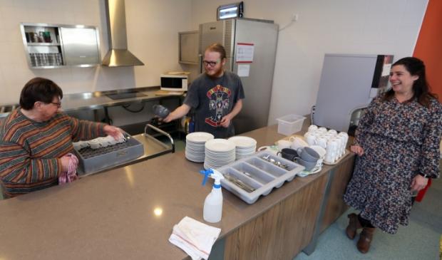 <p>Rick begeleidt Sjaan (l) bij het werk in de kantine. Jobcoach Dani kijkt toe. &quot;Mensen versterken in hun eigen kracht, dat is ons doel.&quot;</p>