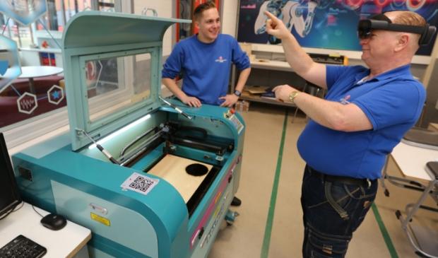 Onderwijsassistent Peter Geerts (r) probeert de hololens uit, op aanwijzing van medewerker techniekpromotie Mees Berkhout.