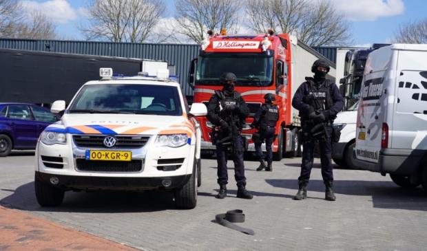 <p>Zwaarbewapende agenten houden de wacht bij een bedrijfspand aan de Lorentzstraat.</p>