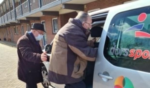 <p>Gerard Webbers wordt door vrijwilliger Jan Vink in de auto geholpen.</p>