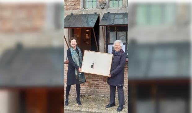 <p>Conservator Julie Hengeveld en mevrouw Van Erp Taalman Kip-Nieuwenkamp, kleindochter van W.O.J. Nieuwenkamp laten een van de tekeningen van W.O.J. Nieuwenkamp zien.&nbsp;</p>