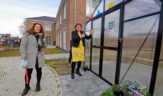 Wethouder Annette Groot verricht de officiële openingshandeling van de tuinkas; links locatiemanager van het Icarushuis Linda Hulscher.