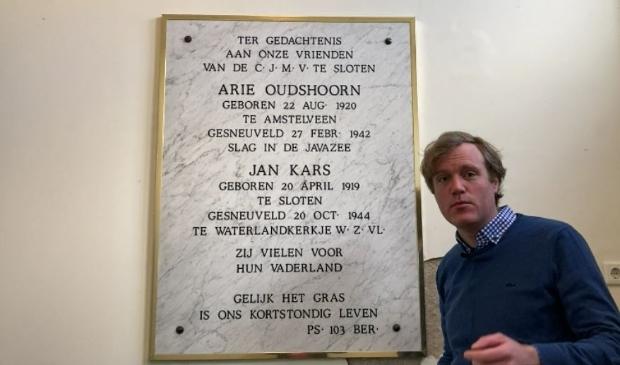 <p>Dominee Martijn van Leerdam bij de plaquette in de Sloterkerk.</p>