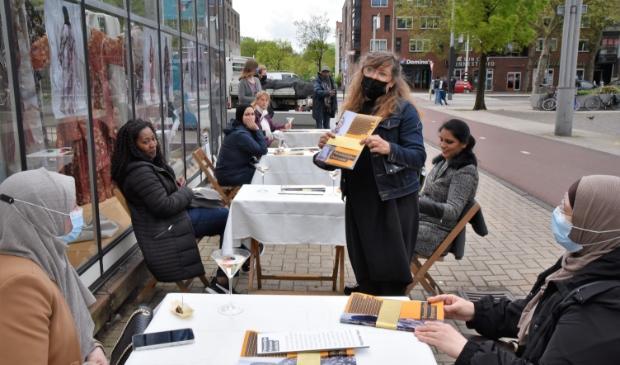 <p>Fiona de Bell reikt de gebundelde verhalen en foto&rsquo;s uit aan de ondernemers en Westerpost.</p>