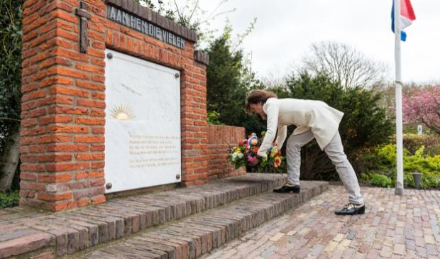 <p>Voorzitter van Parel aan Zee, Marieke Sibarani, legt een bloemstuk neer bij het oorlogsmonument</p>