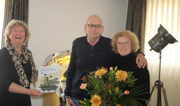 <p>Ina Broekhuizen overhandigt het eerste jaarboek aan Fons en Rina Loos. </p>