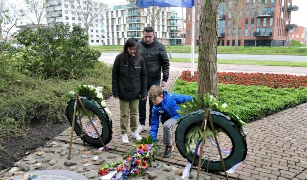 <p>Sven Lekic en Kim Broekhuijsen van Trifolium leggen bloemen bij het monument aan de Jaagweg. Achter hen meester Dennis.</p>