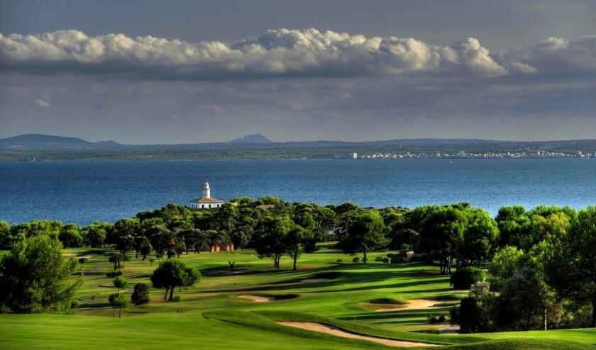 De zevende hole van Alcanada, de signature-hole met adembenemend uitzicht op de markante vuurtoren net voor de kust.