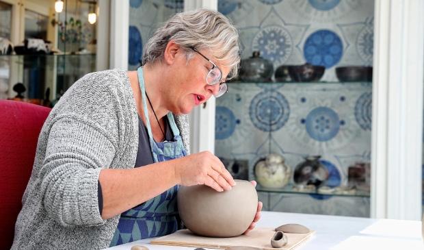 <p>Keramiste Gerdien Noordeloos in haar atelier waar zij werkt aan een urn.</p>