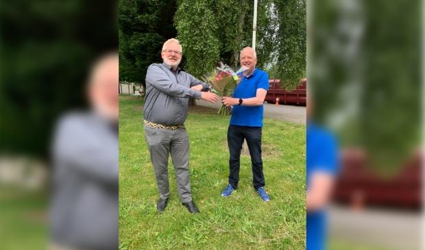 <p>Voorzitter Aalt Bruinekool (r) van CDA-Heemskerk zet John van Nimwegen in de bloemetjes op de dag na zijn verkiezing tot lijsttrekker.</p>