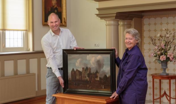 <p>Eric Zwart overhandigt symbolisch het schilderij aan Rina van Rooij.</p>