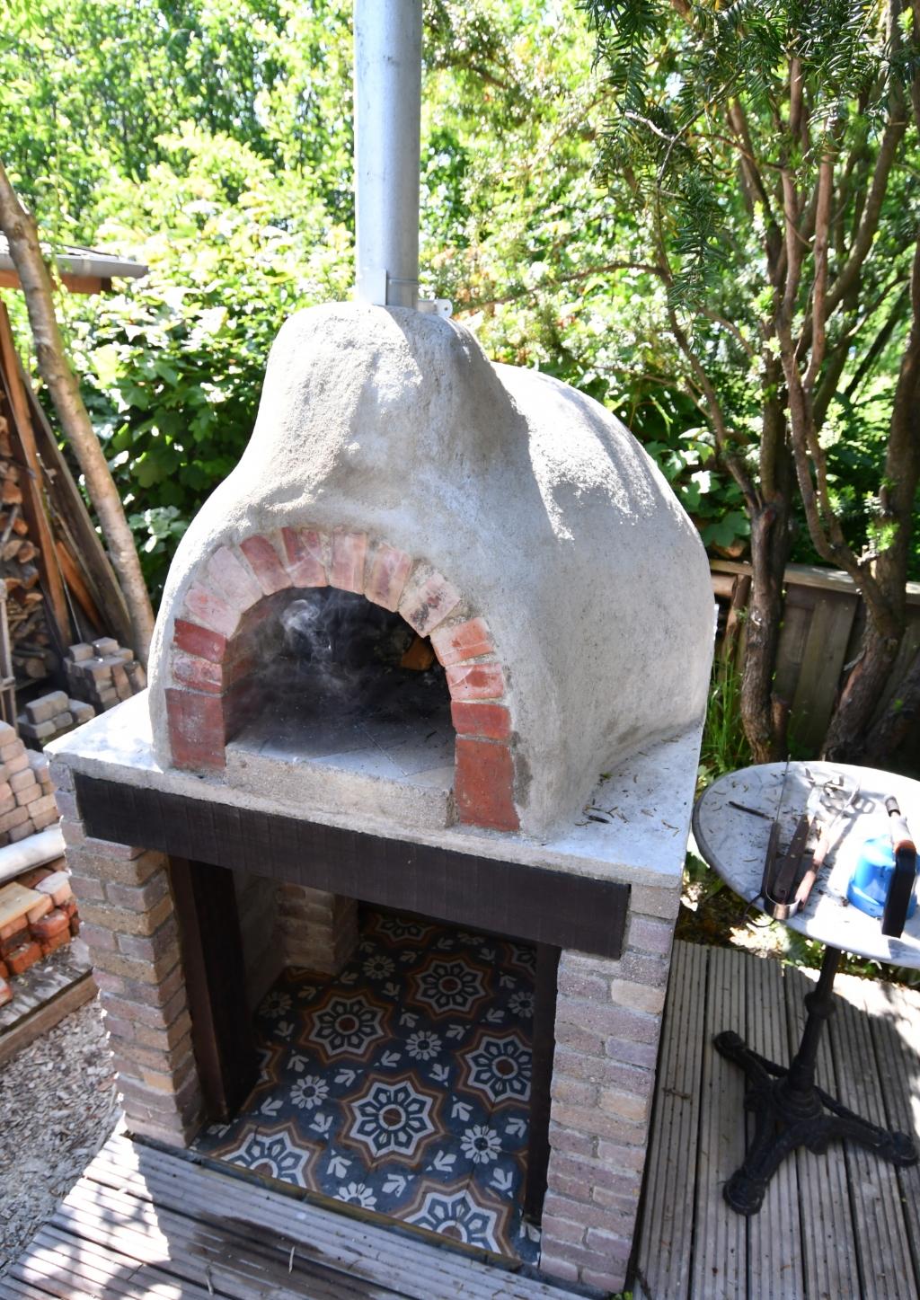 Zelfs een pizzaoven ontbreekt niet in de tuin van Jenny. ('De deur moet er nog in, ik ben hem aan het instoken', aldus haar man)  (Foto: Dirk Karten) © rodi