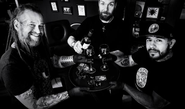 <p>Tatoe&euml;erders Marc Forster en Luis Schaft helpen caf&eacute;houder Sjoerd Beekes met een tattoo flash dag/veiling. </p>