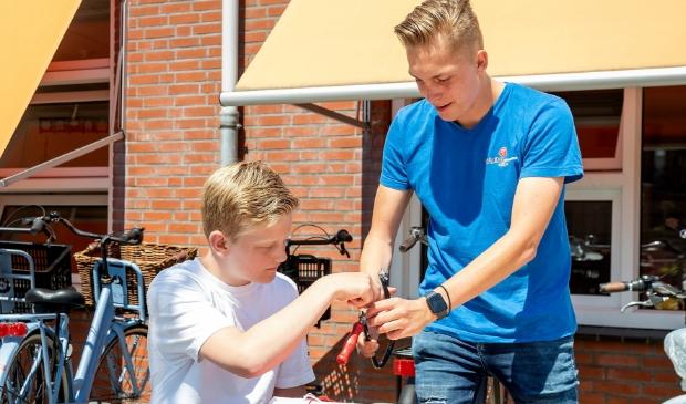 Mees Berkhout, techniekpromotor van het Johannes Bosco, leert Finn, leerling van de Zonnewijzer, hoe hij moet werken met een figuurzaag.