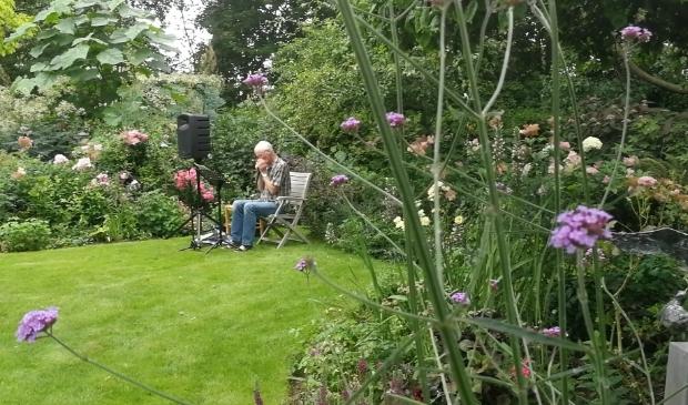 <p>Koos Konijn zorgt voor sfeervolle muziek met zijn mondharmonicas in de tuin.</p>