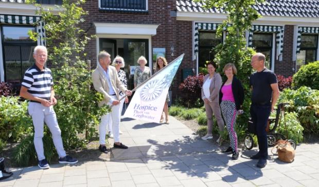 <p>In aanwezigheid van bestuursleden Cees Verkade (l) en Klaas Kwadijk (r), de co&ouml;rdinatoren en de communicatiegroep, bevestigen bestuursvoorzitters Kees Sietsema en Corrie Jaarsma de nieuwe vlag.</p>