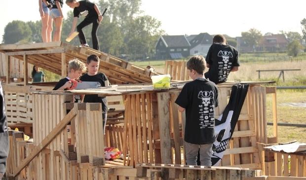 <p>Jongeren zijn druk bezig met het bouwen van een dorp van pallets.</p>
