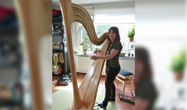 <p>Mirjam begeleidt de zangeres op haar harp.</p>