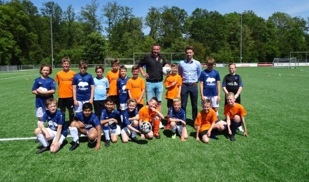 Sponsors René (l) en Marco met de teams van Reflector (in oranje shirts) en de Familieschool. Beide teams samen op de foto; ook dat zorgt voor verbinding. De Reflector won de wedstrijd overigens met 3-0.
