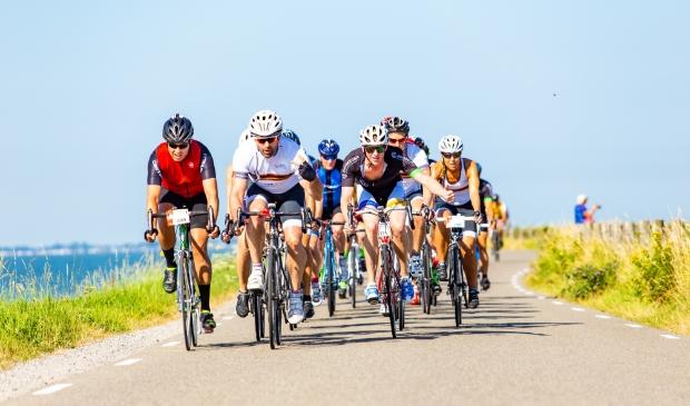 Wielrenners toeren door een schitterend landschap, over de Westfriese Omringdijk.
