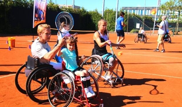 <p>Esther Vergeer helpt de jonge Jasmine met de sport.</p>