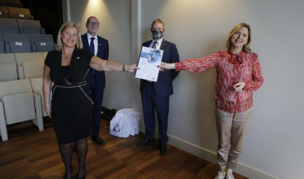 <p>Demissionair minister Cora van Nieuwenhuizen (r) overhandigt het rapport aan Executive Secretary Corinne Mulder.</p><p><br></p><p><br></p>
