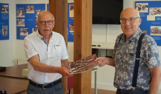 <p>Egbert Ottens (l) ontvangt het kwartaalblad uit handen van de voorzitter van Oud Hoorn, Jaap van der Hout.</p>
