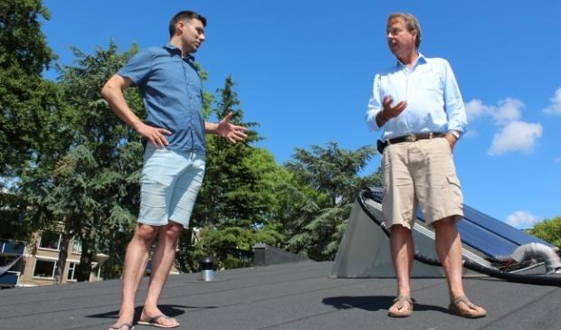 <p>Energiecoaches Robert Vaane (38) en Frank van Oudenhove (63) praten over duurzaamheidstoepassingen, op het dak.</p>