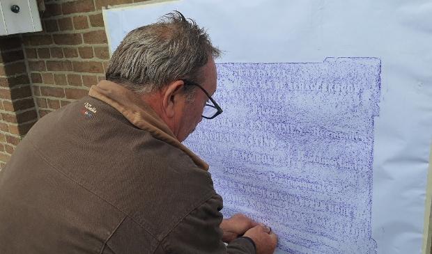 <p>Ed Oosterhuis brengt door &lsquo;rubben&rsquo; de tekst van de gevelsteen over op papier. </p>