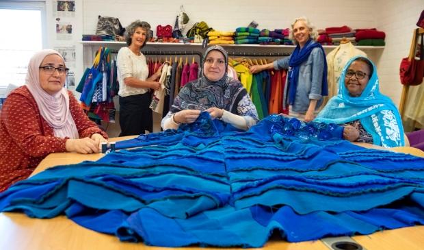 <p>Tara, Israa en Akberet (v.l.n.r.) werken aan de jas die in het kader van Wereldvluchtelingendag tentoongesteld wordt. Op de achtergrond Marilou Evelo (l) en Gerda Schoenmaker.</p>