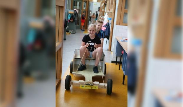 <p>Basischoolleerlingen van t Skitteljacht maken een rit met een zelfgtemaakte auto ter promotie van de elektrische deelautos&#39;s.</p>