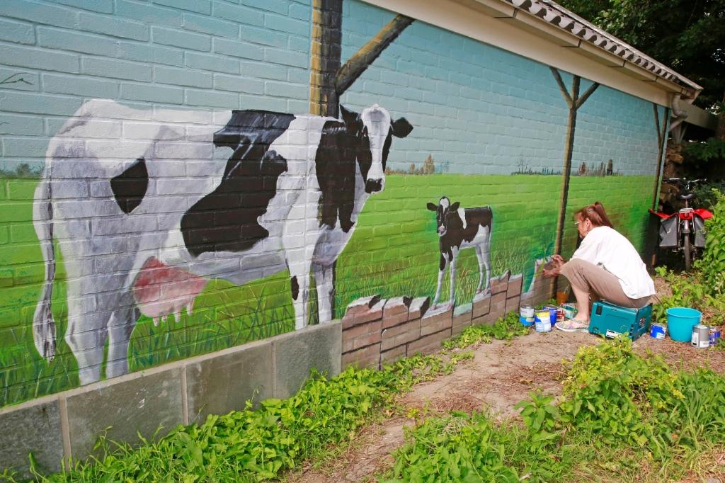 Marian met de koe en kalf in de wei. (Foto: Theo Annes) © rodi